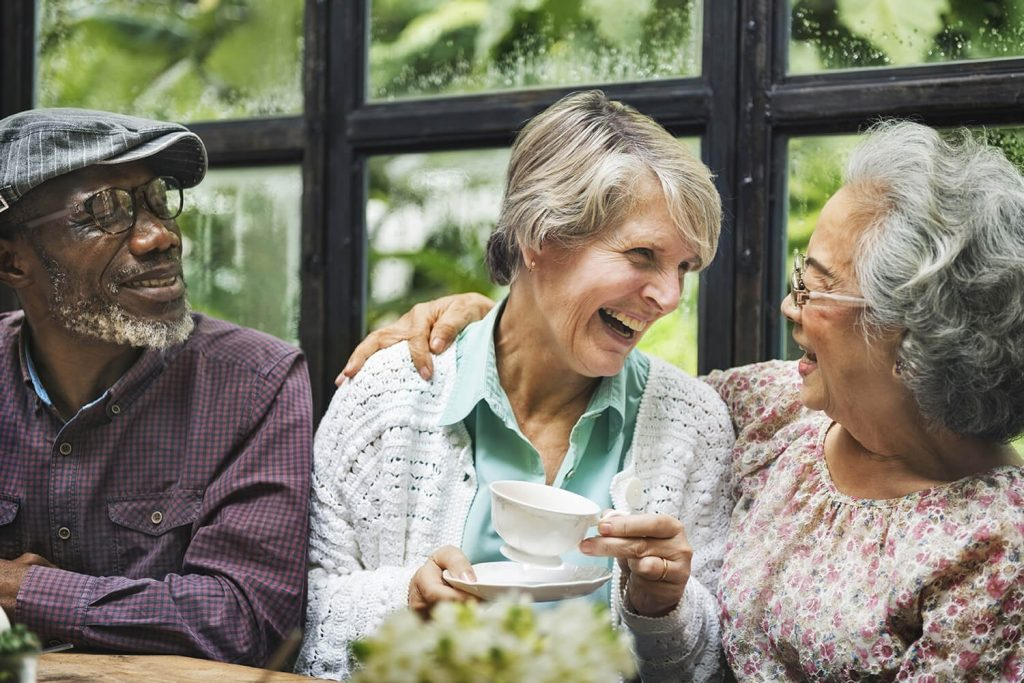 three residents laugh and enjoy community together